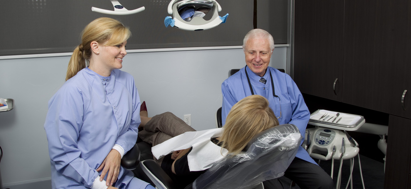 Dr. Gordon J. Christensen (right) and his assistant (left) sit chairside, consulting a dental patient (seated, center).